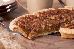 Slice of Pecan Pie. Closeup of a slice of pecan pie on a wooden platter Stock Photo