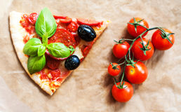 Slice of Pepperoni pizza with fresh tomatoes on brown baking pap. Er background, top view. Banner or wallpaper Stock Photos