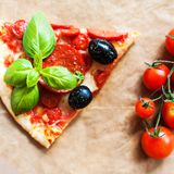 Slice of Pepperoni pizza with fresh tomatoes on brown baking pap. Er background, top view. Banner or wallpaper Royalty Free Stock Photo