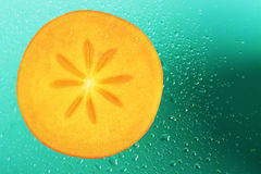 Slice of persimmon. With water droplets Stock Image