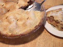 Slice of pie. Freshly baked apple pie with slice cut on a butcher block table. focus on slice of pie. shallow depth of field Stock Photography