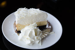 Slice piece of vanilla cake topping with white chocolate chips. On disk Royalty Free Stock Photos