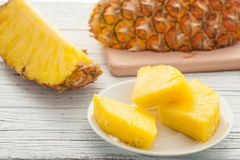 Slice of pineapple in white plate on wooden table Royalty Free Stock Photo