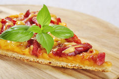 Slice of pizza. Closeup on a wooden cutting board stock image