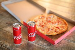Slice pizza in box and can of coca-cola royalty free stock image