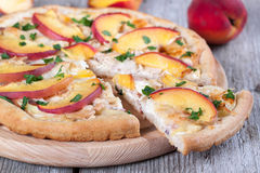 Slice of pizza with chicken and peaches on a wooden board. Slice of pizza with chicken and peaches Royalty Free Stock Photos