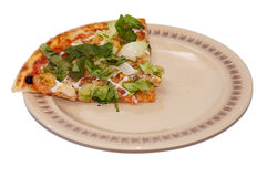 Slice of pizza with green letuce on the plate.  Stock Image