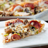 Slice of pizza on a plate with pereroni and black royalty free stock image