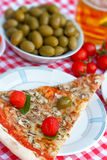 Slice of pizza served on plate with glass of beer Royalty Free Stock Photography