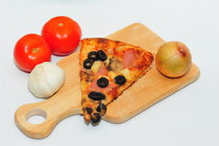 Pizza slice and ingredients. A slice of pizza served on a wooden board next to some ingredients Stock Image