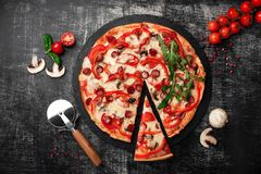 A slice of pizza on a spatula with smoked sausages, cheese, mushrooms, cherry tomatoes, bell peppers on a stone. A slice of pizza on a spatula with smoked royalty free stock image