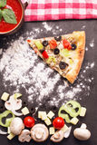 Slice of pizza vegetariana on table with flour, tomatoes, mushro Royalty Free Stock Photo