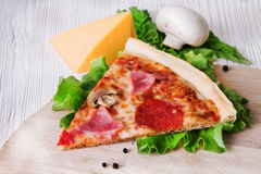 Slice of pizza on a white board Royalty Free Stock Image