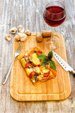 Slice of pizza is on a wooden board. A slice of pizza is on a wooden board on a background of a glass of wine Stock Photography