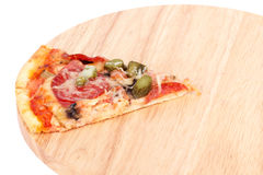 Slice of pizza on wooden cutting board Royalty Free Stock Photos