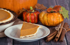 Slice of pumpkin pie with autumn decorations Stock Images