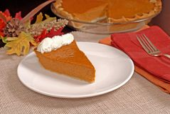 Slice of pumpkin pie with autumn leaves resting in background Royalty Free Stock Photos