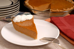 Slice of pumpkin pie with extra plates resting in background alo Stock Photo