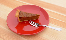 Slice of pumpkin pie with a fork on a plate Stock Photo