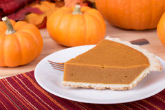 Slice of Pumpkin Pie. With pumpkins in background Royalty Free Stock Photos