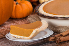 Slice of a pumpkin pie and pumpkins on the background Stock Photos