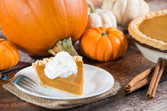 Slice of a pumpkin pie and pumpkins Royalty Free Stock Photos