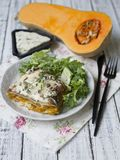 Slice of Pumpkin and Spinach Lasagne with blue cheese and salad on a White Wooden Table. Selective focus, copy space royalty free stock images