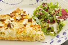 A slice of quiche with leek and feta or goats cheese on a plate with crispy leaf green salad. Vegetarian food in close up. Image stock image