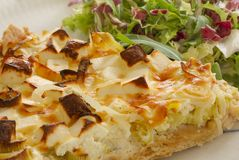 A slice of quiche with leek and feta or goats cheese on a plate with crispy leaf green salad. Vegetarian food in close up. Image stock photo