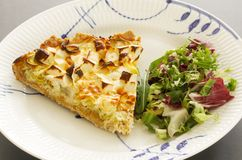A slice of quiche with leek and feta or goats cheese on a plate with crispy leaf green salad. Vegetarian food image close up. A slice of quiche with leek and stock photography
