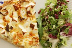 A slice of quiche with leek and feta or goats cheese on a plate with crispy leaf green salad. Vegetarian food in top view close up. Image stock images