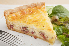 Slice of Quiche Lorraine on a Plate with Salad. A slice of classic Quiche Lorraine, or bacon and egg flan, on a plate with green salad Stock Images