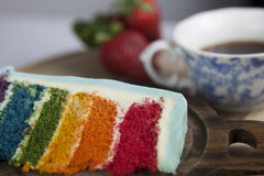A Slice of Rainbow Cake with some Strawberries and Cup of Coffee. A slice of rainbow cake with some wood and strawberries in the background royalty free stock images