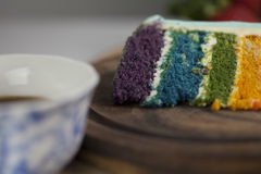 A Slice of Rainbow Cake with some Strawberries and Cup of Coffee. A slice of rainbow cake with some wood and strawberries in the background stock photos