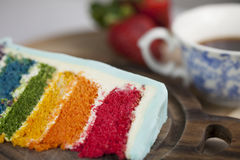 A Slice of Rainbow Cake with some Strawberries and Cup of Coffee. A slice of rainbow cake with some wood and strawberries in the background Stock Images