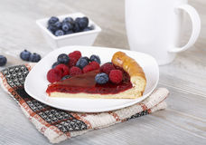 Slice of raspberry pie with fresh berries on a plate. Fresh raspberry pie, tasty filling, fresh raspberries and blueberries Stock Image