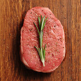 Slice of raw beef with fresh rosemary Royalty Free Stock Photography