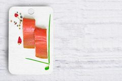 Slice of raw red fish, sea chum on white wooden Board, healthy eating, top view,. Copy space Royalty Free Stock Photography