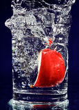 Slice of red apple falling down in glass Stock Photo