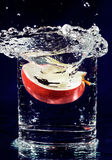Slice of red apple falling down in water Stock Image