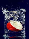 Slice of red apple falling down in water Stock Images