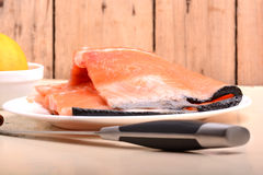 Slice of red fish salmon with knife abd lemon Royalty Free Stock Image