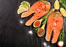 Slice of red fish salmon with lemon, rosemary on black stone background with copy space for your text. Top view. Slice of red fish salmon with lemon, rosemary Royalty Free Stock Images
