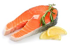 Slice of red fish salmon with lemon and rosemary isolated on white background.  Royalty Free Stock Images