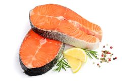Slice of red fish salmon with lemon, rosemary and peppercorn isolated on white background.  Royalty Free Stock Photos