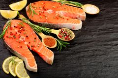 Slice of red fish salmon with lemon, rosemary on black stone background with copy space for your text. Top view. Slice of red fish salmon with lemon, rosemary Stock Images