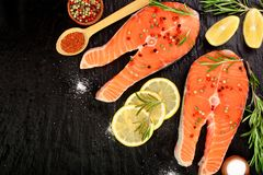 Slice of red fish salmon with lemon, rosemary on black stone background with copy space for your text. Top view. Slice of red fish salmon with lemon, rosemary Royalty Free Stock Photography