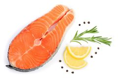Slice of red fish salmon with lemon, rosemary and peppercorns  on white background. Top view. Flat lay.  Stock Photos