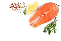 Slice of red fish salmon with lemon, rosemary  on white background with copy space for your text. Top view. Slice of red fish salmon with lemon, rosemary and Royalty Free Stock Images