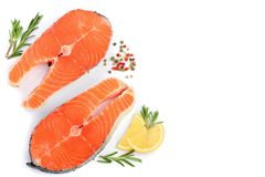Slice of red fish salmon with lemon, rosemary  on white background with copy space for your text. Top view. Slice of red fish salmon with lemon, rosemary and Royalty Free Stock Image
